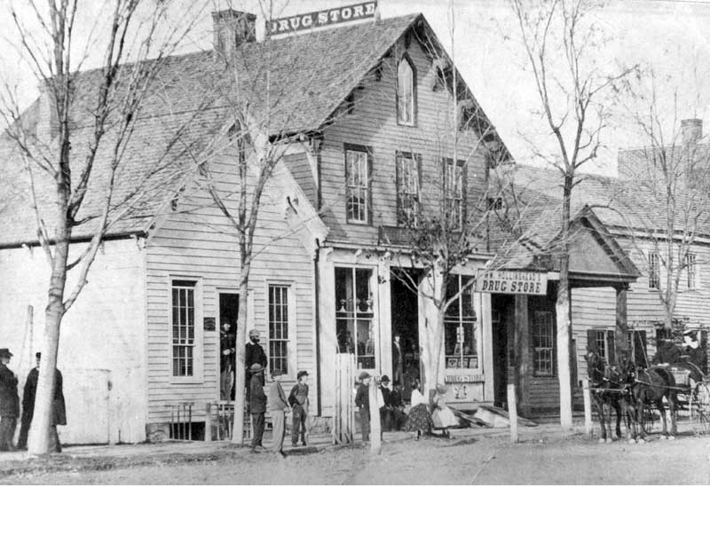 The Hollinshead Drug Store, shown in 1865, was located on Main Street near 7th Street in Stroudsburg. The first building on the left was the office of Dr. Jackson. The carriage on the right is in front of Judge Dreher's office.